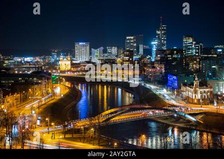 Vilnius, capital of Lithuania, night scenic aerial panorama of modern business financial district architecture buildings with Neris river and bridge