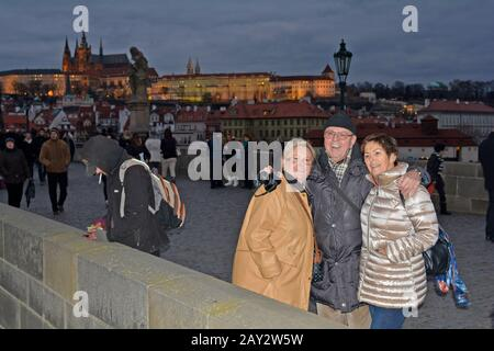 Prague, Czech Republic - December 2nd 2015: Unidentified tourists by sightseeing on  Charles bridge over river Moldau to castle and St. Vitus cathedral - Stock Photo