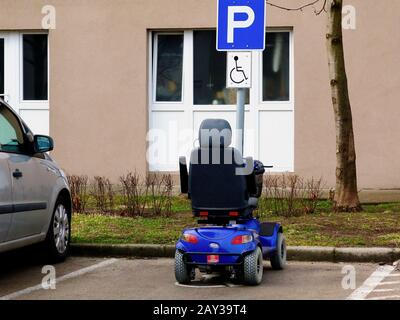 blue electric motorised disability or handicap scooter in handicap parking stall. blue and white parking area sign on aluminum pole. parking symbol. - Stock Photo