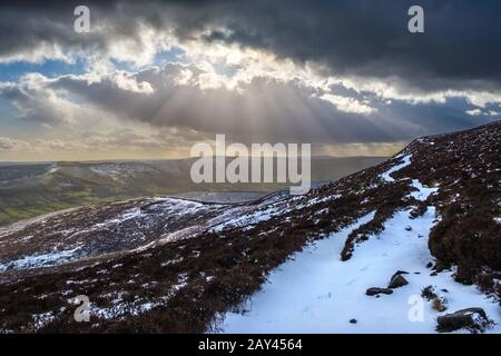 Sunlight breaking through clouds on a winter afternoon. Kinder Scout, Peak District National Park,UK - Stock Photo