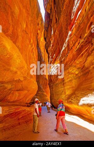 Petra, Jordan - May 23, 2009:  Walking tourists in gorge between cliffs in Petra - Stock Photo