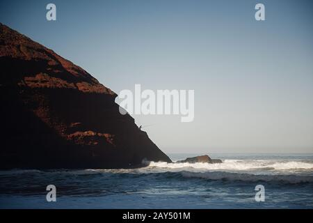 Legzira dramatic natural stone arches reaching over the sea, Atlantic Ocean, Morocco, Africa. Fisherman on the edge. - Stock Photo