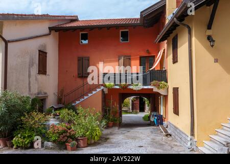 Brightly colour-washed houses and a pretty courtyard, Duino, Province of Trieste, Friuli-Venezia-Giulia, Italy - Stock Photo