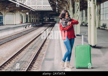 Photo of attractive young woman waits train at railway station, dressed in knitted sweater and jeans, stands near green bag, looks at watch. Pleased p - Stock Photo