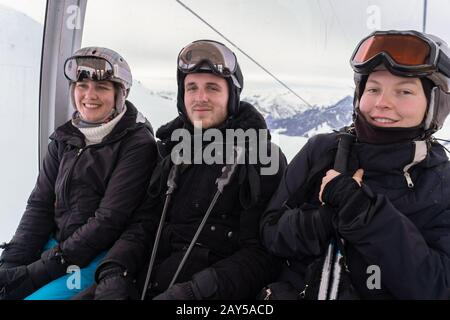 Young adults sitting in a cableway running up a slope, wearing helmet and goggles and holding sticks with snow mountain in background on a cloudy day