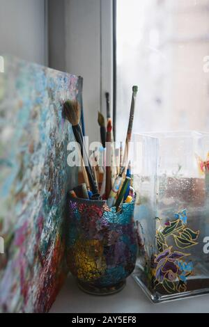 A variety of artist brushes and pencils are on the windowsill in a beautiful glass made of colored glasses.  - Stock Photo