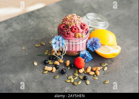 Delicious raspberry ice cream with pumpkin seeds and hempseed, decorated with blue cornflowers, black currant, sliced lemon on grey surface. Tasty des - Stock Photo