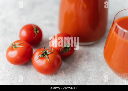 Close up shot of four ripe red tomatoes on white background, fresh juice in glasses near. Healthy lifestyle. Delicious drink made of vegetables - Stock Photo