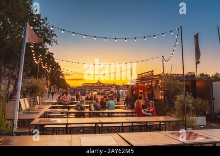28 July 2019, Paris, France: Cafe on the promenade in Paris during sunset - Stock Photo
