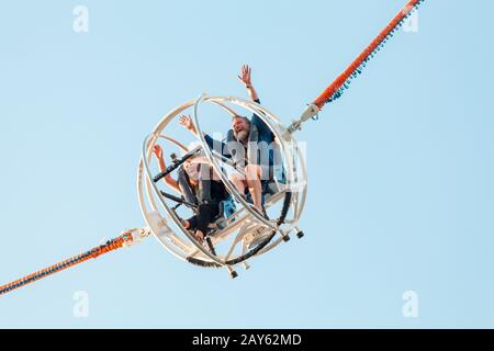 28 July 2019, Paris, France: Couple laughing and rejoicing at Catapult attraction at amusement Park - Stock Photo