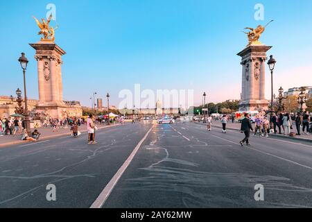 28 July 2019, Paris, France: People walk on the Alexander III bridge during a bright sunset over the Seine. Trip to Paris - Stock Photo