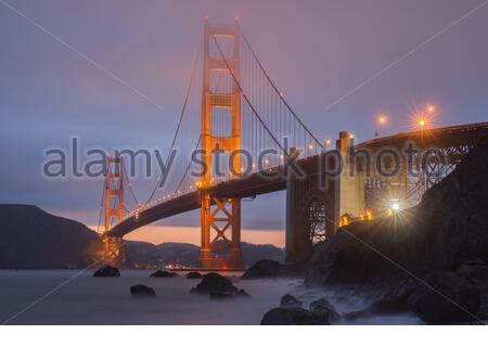 Crack in the clouds behind the Golden Gate Bridge as seen from Marshall's Beach. - Stock Photo