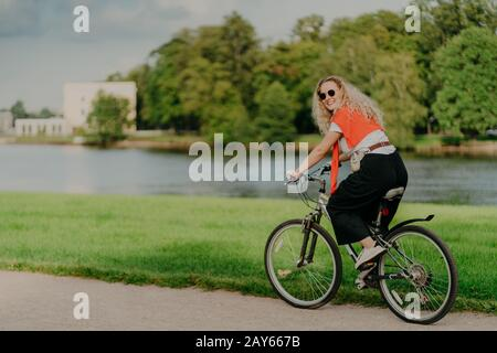 Photo of cheerful woman dressed casually, rides bicycle, looks aside, has happy expression, wears shades, poses near river, green lawn and trees, some - Stock Photo
