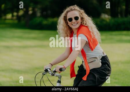 Photo of curly European woman keeps hands on handlebar of bicycle, travels outdoor in park, wears shades, casual t shirt and black trousers, smiles po - Stock Photo