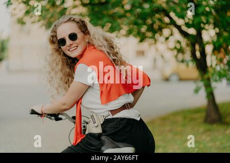 Photo of delighted woman poses back at camera, rides bicycle outdoor, wears sunglasses, t shirt and sweater on shoulders, poses near green tree, has t - Stock Photo