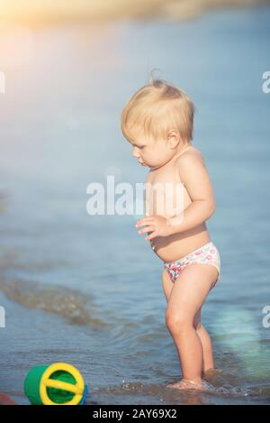 Cute baby playing on the sandy beach and in sea water. - Stock Photo