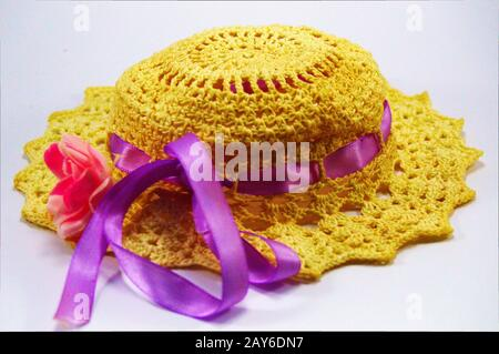 Hat realized by means of hooks with a pink ribbon. - Stock Photo