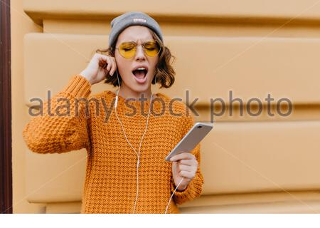 Sleepy curly girl in sweater going to run in morning and wearing earphones. Tired young woman in hat listening music on phone after sport exersizes outdoor. - Stock Photo