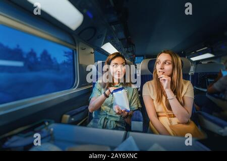 Two girl friends passengers sitting in first class train at night time, and eating chips
