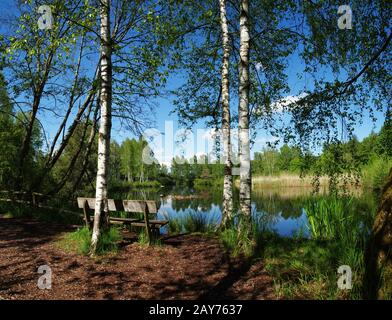 Seat for resting at the lake in the Pfrunger Ried - Stock Photo
