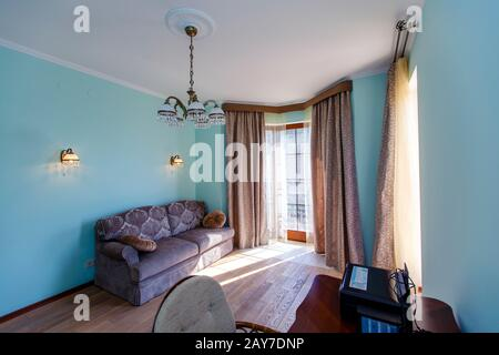 The interior of the room is in a classic style with blue walls, a sofa table and large Windows with curtains. - Stock Photo