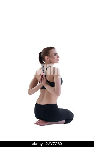 Yuong girl doing yoga posing with back to viewer