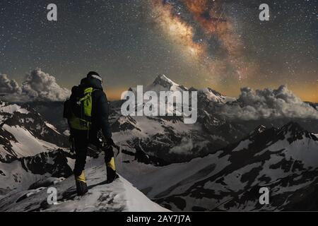Night photo climber stands on top of a mountain in the snow and looks at the surrounding mountains over which the starry sky and - Stock Photo