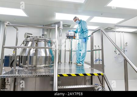 scientist look in steel tank in laboratory - Stock Photo