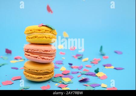 Colorful macarons on trendy pastel blue paper with confetti. tasty pink, yellow and brown macaroons .
