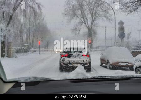 A car is standing in the snow flurry in front of closed railway barriers. - Stock Photo