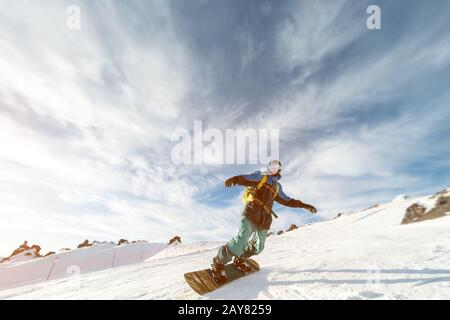 A snowboarder in a ski mask and a backpack is riding on a snow-covered slope leaving behind a snow powder against the blue sky a - Stock Photo