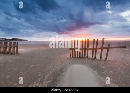 wind blowing sand on Tarifa beach in Spain at sunset - Stock Photo