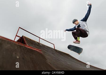 Teenager skateboarder in a cap doing a trick jump on a half pipe on a cloudy sky background - Stock Photo