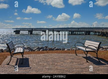 Empty Benches on Patio by Seaside Pier - Stock Photo