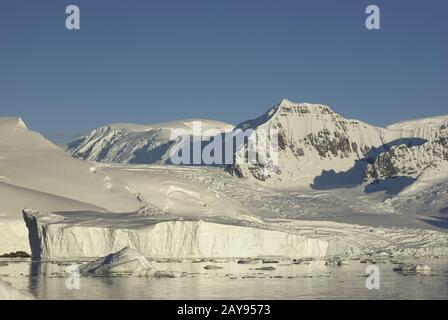 mountains and glaciers of the coast of Antarctica and icebergs in the ocean near it - Stock Photo