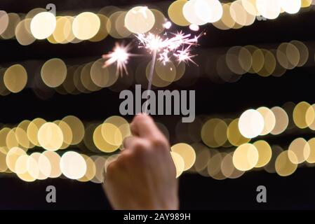 Close up view of woman hands holding sparkler, celebrating new year eve - Stock Photo