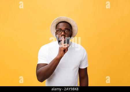 Closeup portrait of handsome bald man placing finger on lips as if to say, isolated on yellow background with copy space