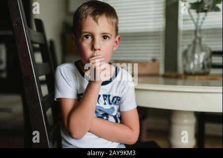 Young Boy Sucking Thumb at the Table in Pajamas in Buda Texas Stock Photo