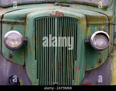 close up of the front of an old abandoned rusting green truck covered in moss - Stock Photo