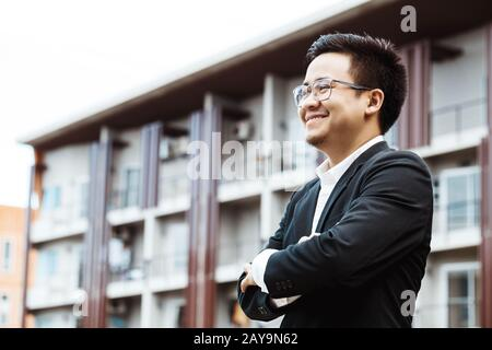 Portrait of a smiling handsome businessman with arms folded - Stock Photo