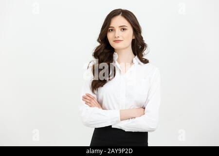 Business Concept: Portrait confident young businesswoman keeping arms crossed and looking at camera while standing against grey - Stock Photo