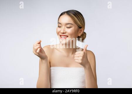 Healthy happy asian woman with pills in hand isolate over white background. - Stock Photo