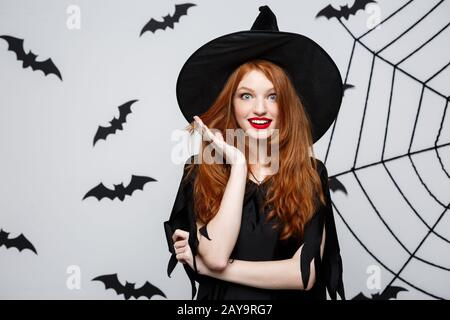 Halloween Concept - Beautiful caucasian witch surprising with something over grey background. - Stock Photo