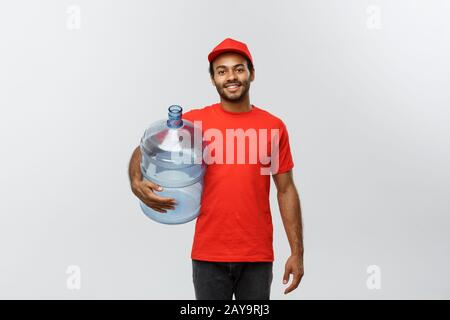 Delivery Concept - Handsome African American delivery man holding water tank. Isolated on Grey studio Background. Copy Space. - Stock Photo