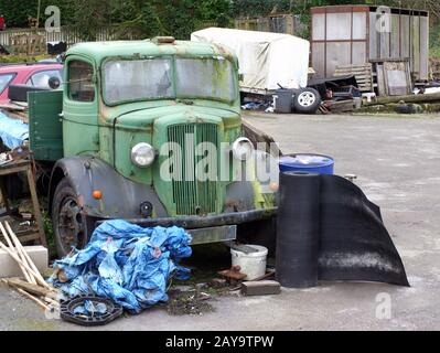 an old rusting green  truck with scrap wood and metal in a rural junkyard - Stock Photo
