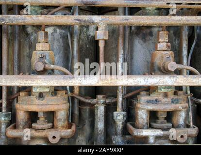 Close up of an old big rusting diesel engine with cylinders and pipes - Stock Photo