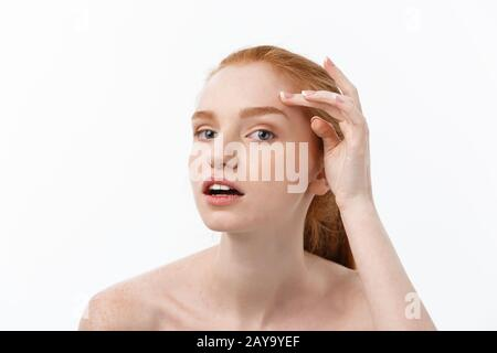 redheaded woman shows fingers on acne on her face. - Stock Photo