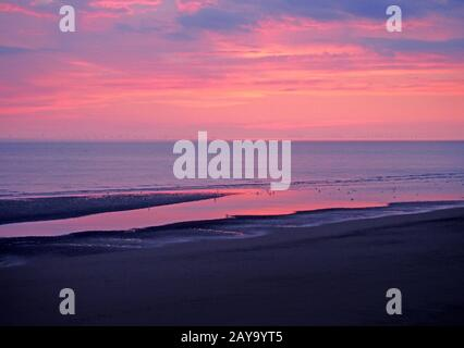 twilight dramatic purple sky over a calm the sea with colorful evening clouds reflected in water - Stock Photo