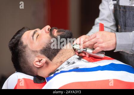 Barber shaving the beard of a handsome bearded man with an electric razor at the barber shop. - Stock Photo