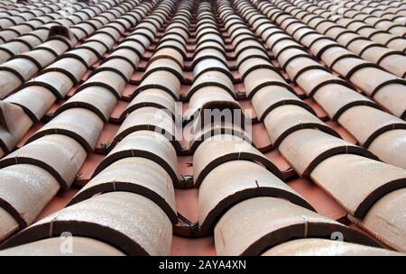 close up perspective view of traditional red clay pantiles on a roof with focus near the foreground - Stock Photo